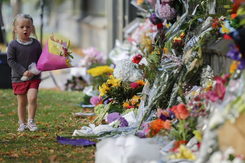 A girl walk to lay flowers on a wall at the Botanical Gardens in Christchurch, New Zealand, Sunday, March 17, 2019.
