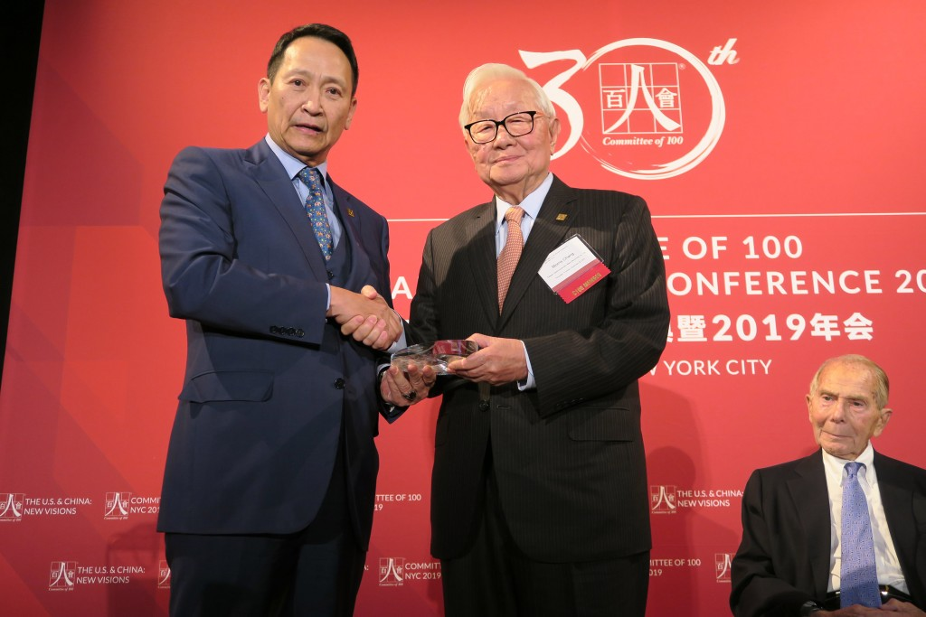 TSMC founder Morris Chang (standing, right) receiving the award from Committee of 100 Chairman Roger Wang (left).