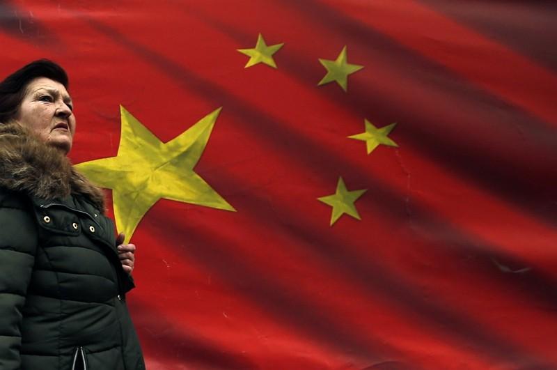塞爾維亞女子路過中國國旗(圖/美聯社)