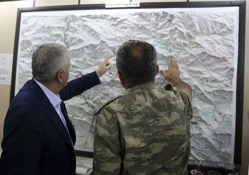 FILE - In this Monday, Sept. 5, 2016 file photo, an army commander informs Turkey's Prime Minister Binali Yildirim, left, on a Turkey-I...