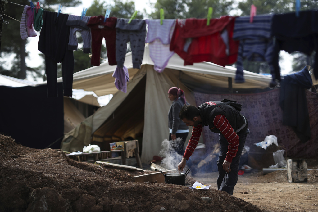 A Syrian man cooks outside his tent at Ritsona refugee camp north of Athens, on Wednesday, Oct. 19, 2016. About 600 people, mostly fami...