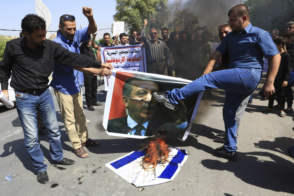 FILE - In this Friday, Oct. 14, 2016 file photo, Iraqi protesters burn a poster depicting Turkish President Recep Tayyip Erdogan and Is...