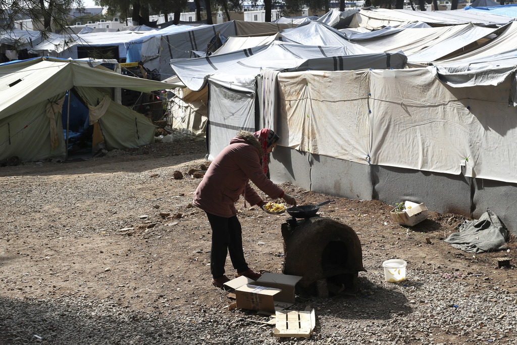A Syrian woman cooks outside her tent at Ritsona refugee camp north of Athens, on Wednesday, Oct. 19, 2016. About 600 people, mostly fa...