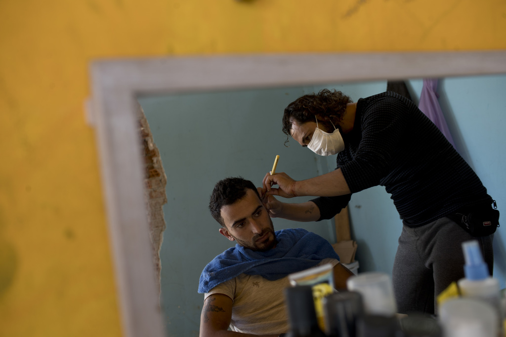 A barber shaves another refugee at Ritsona refugee camp north of Athens, on Wednesday, Oct. 19, 2016. About 600 people, mostly families...