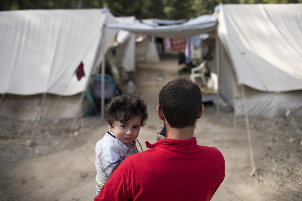 A Syrian man holds his eight month old daughter at Ritsona refugee camp north of Athens, on Wednesday, Oct. 19, 2016. About 600 people,...