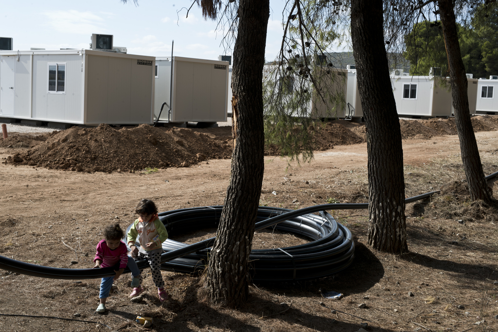 Children play on a plastic pipe to be used for water distribution in front of prefabricated homes under construction at Ritsona refugee...