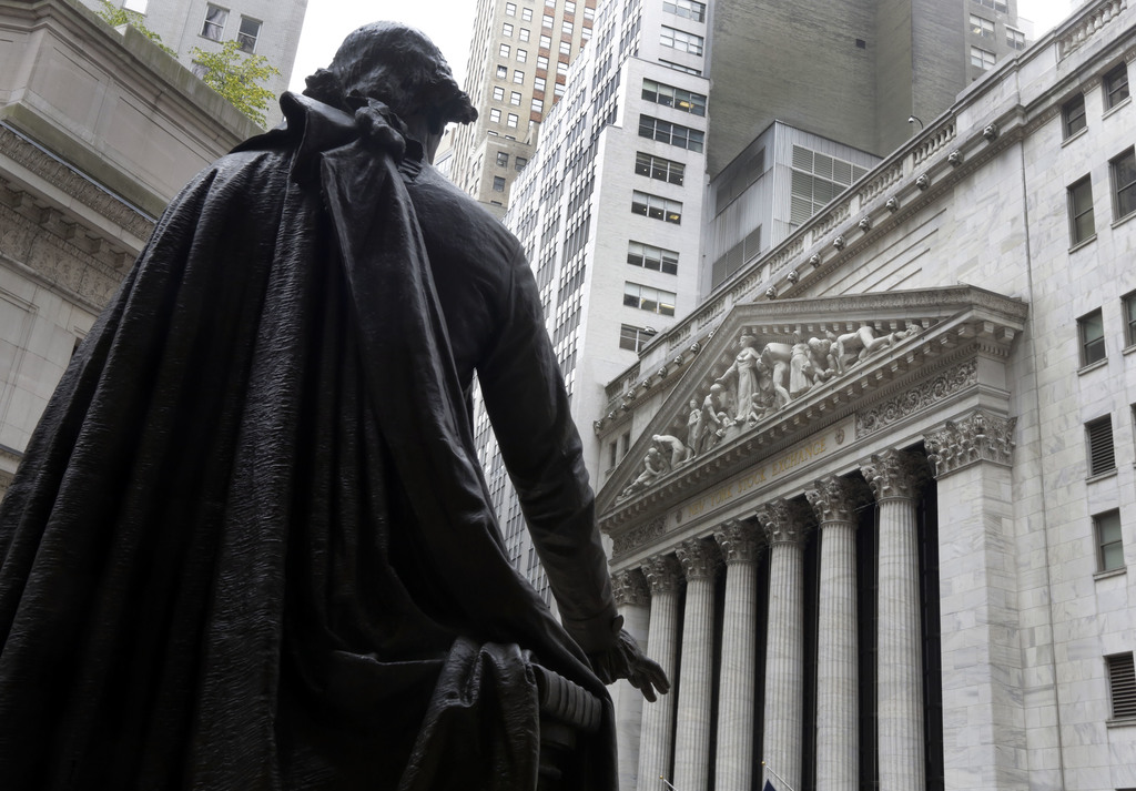 FILE - In this Oct. 2, 2014, file photo, the statue of George Washington on the steps of Federal Hall faces the facade of the New York Stock Exchange....