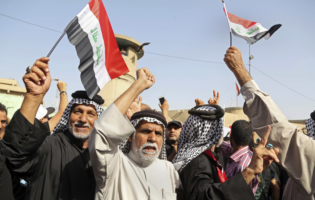 FILE  In this Tuesday, Oct. 18, 2016 file photo, supporters of Shiite cleric Muqtada al-Sadr wave national flags during a demonstration...