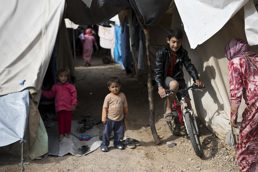 A boy drives his bicycle among tents at Ritsona refugee camp north of Athens, on Wednesday, Oct. 19, 2016. About 600 people, mostly fam...