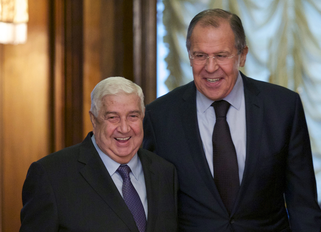Russian Foreign Minister Sergey Lavrov, right, welcomes his Syrian counterpart Walid al-Moallem during their meeting in Moscow, Russia,...