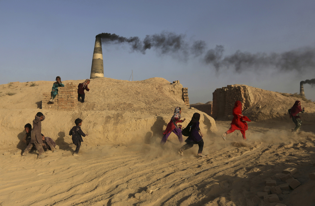 In this Oct. 3, 2016 photo, Afghan children, play at a brick factory in Deh Sabz, on the outskirts of Afghanistan's capital, Kabul. Eac...