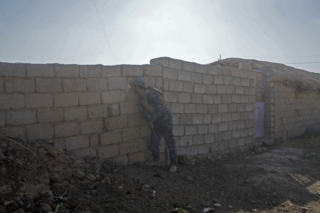 An Iraqi Federal Police officer looks out through a hole in the wall as his team secures an area in the town of Shura, some 30 kilomete...