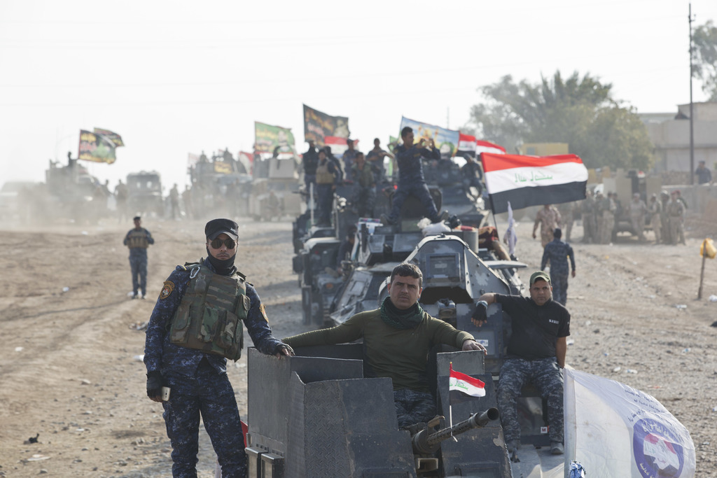 Iraqi Federal Police officers observe as air and ground strikes hit the town of Shura, some 30 kilometers south of Mosul, Iraq, Saturda...