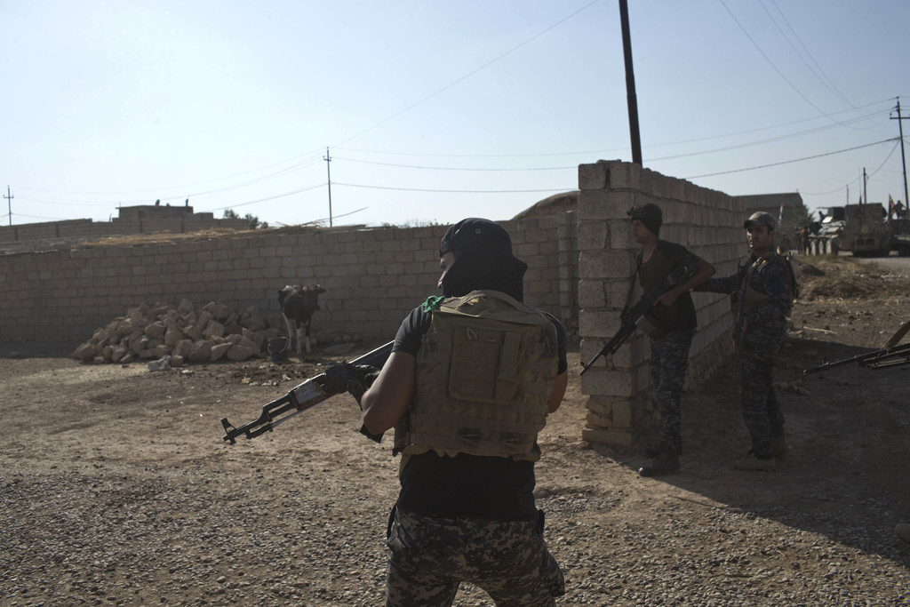 Iraqi Federal Police officers enter a compound in the town of Shura, some 30 kilometers south of Mosul, Iraq, Saturday, Oct. 29, 2016. ...