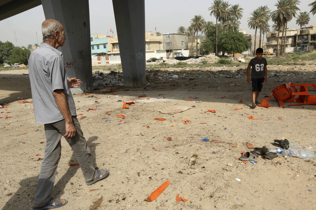 Civilians gather at the site of a suicide bomb attack in Baghdad's western Iskan neighborhood, Iraq, Saturday, Oct. 29, 2016. Iraqi off...