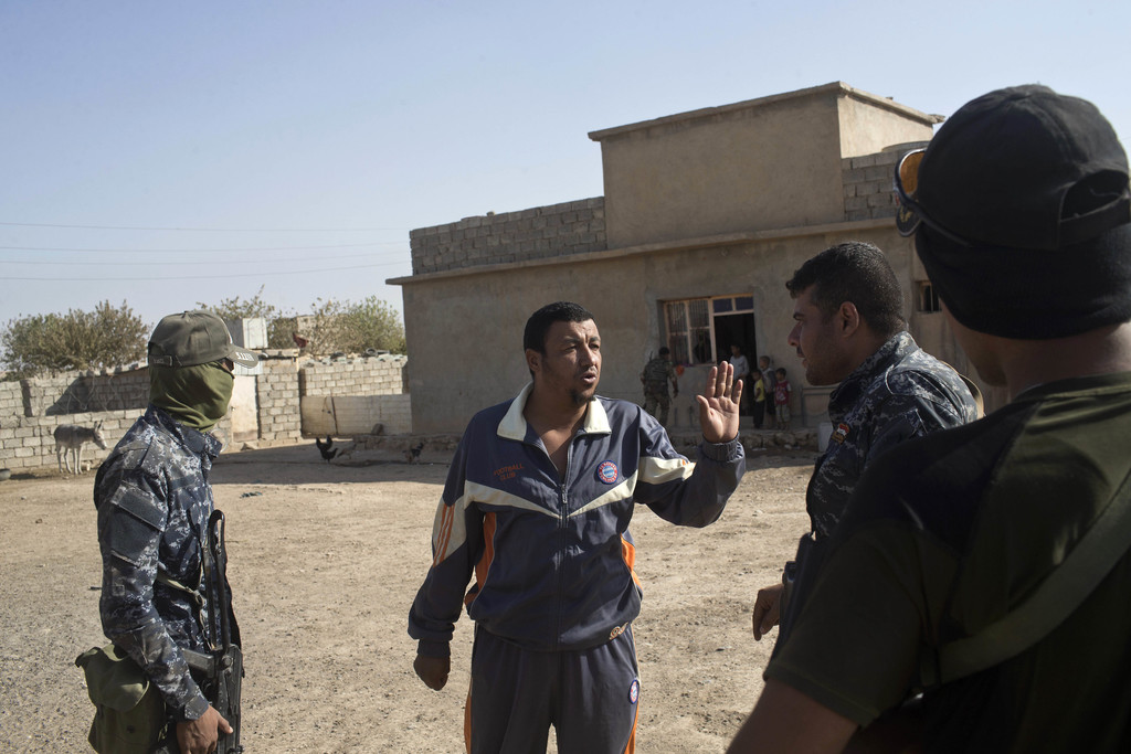 A local resident talks to Iraqi Federal Police officers after they have entered the town of Shura, some 30 kilometers south of Mosul, I...