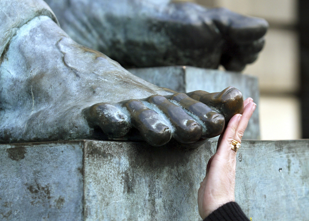 FILE - In this Feb. 6, 2007, file photo, a woman touches the toe of the bronze statue of Scottish philosopher David Hume in Edinburgh, ...