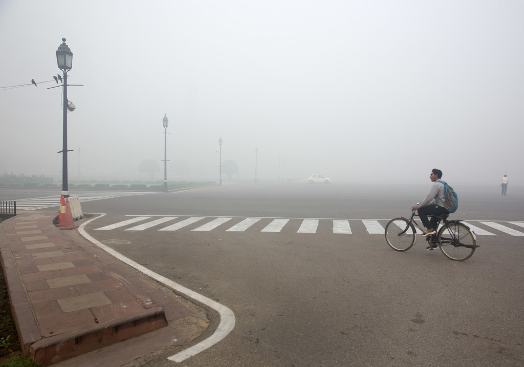 A cyclist rides on a road enveloped by smoke and smog, on the morning following Diwali festival in New Delhi, India, Monday, Oct. 31, 2