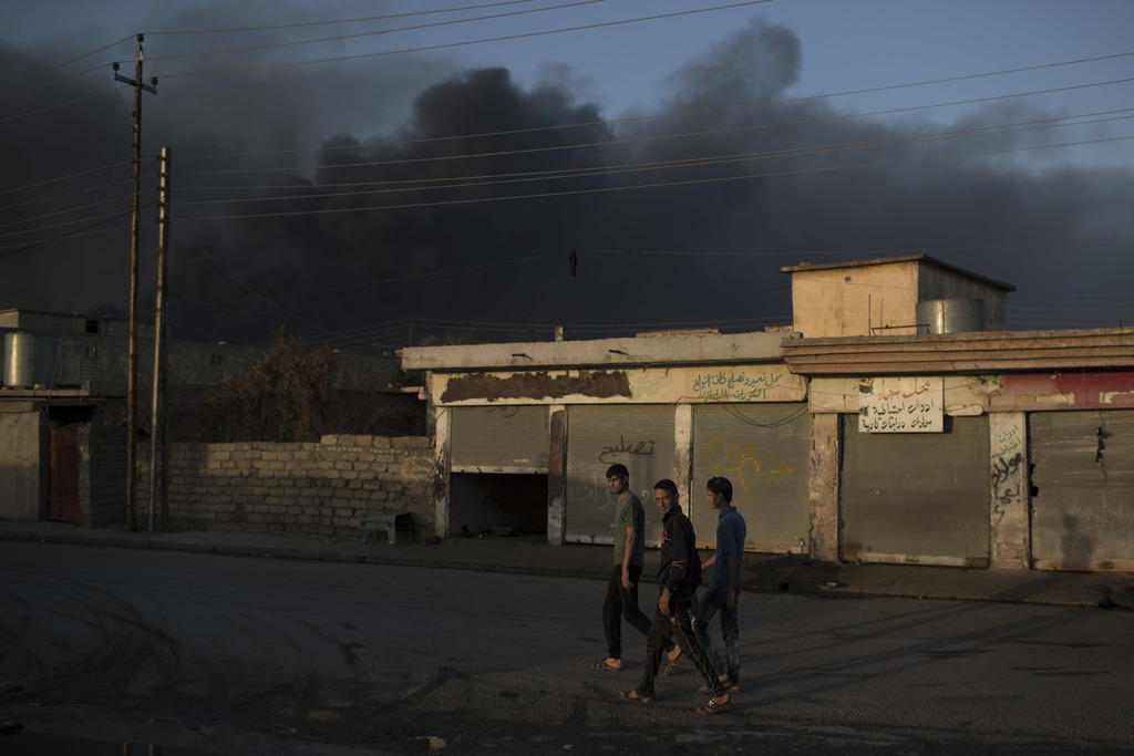 People walk on a street as smoke rises from burning oil fields in Qayara, some 50 kilometers south of Mosul, Iraq, Monday, Oct. 31, 201...