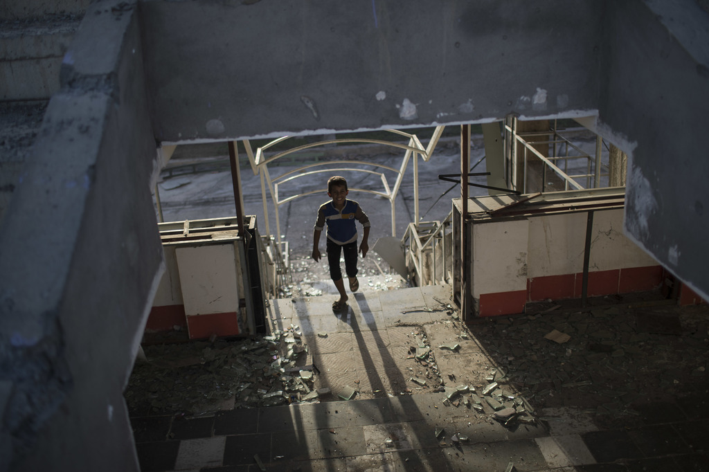 A boy plays inside a destroyed building in Qayara, some 50 kilometers south of Mosul, Iraq, Monday, Oct. 31, 2016. For two weeks, Iraqi...