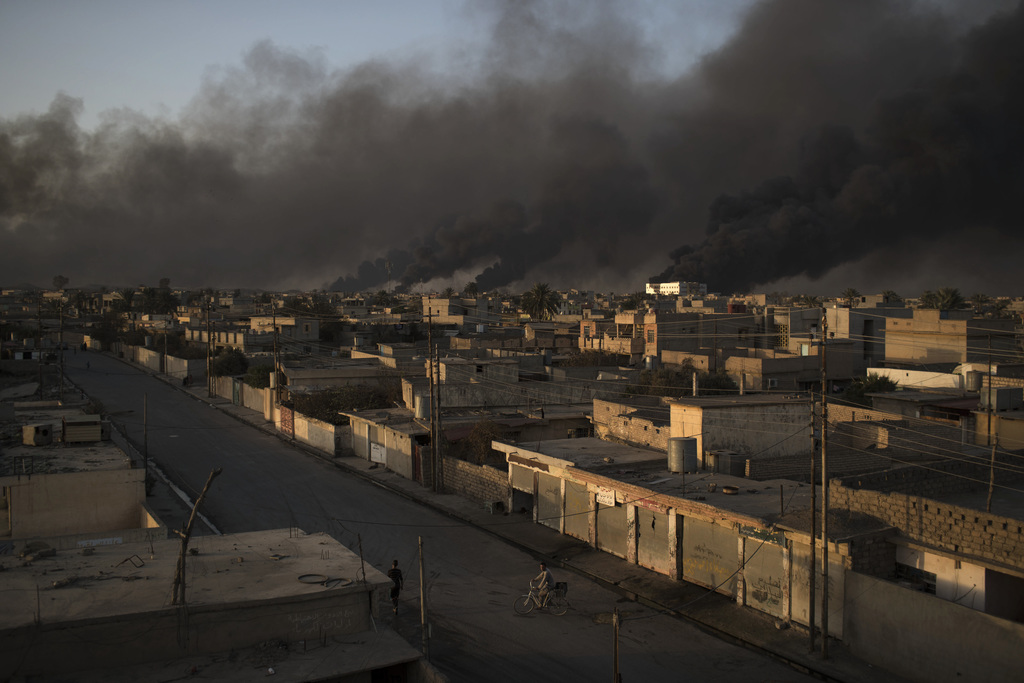 A man rides his bike on a street as smoke rises from burning oil fields in Qayara, some 50 kilometers south of Mosul, Iraq, Monday, Oct...