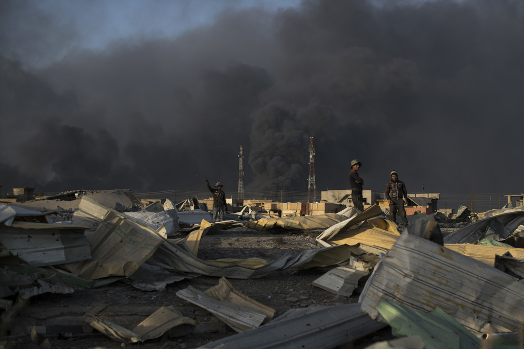 People stand among debris as smoke rises from burning oil fields in Qayara, some 50 kilometers south of Mosul, Iraq, Monday, Oct. 31, 2...