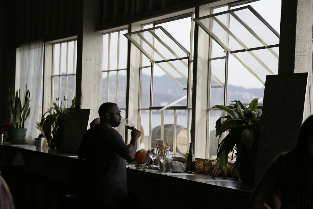 In this photo taken Friday, Oct. 7, 2016, a man looks out toward San Francisco Bay while tasting wine at the Riggers Loft Wine Company ...