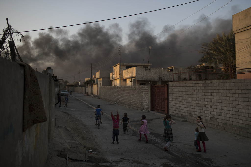 Children play on a street as smoke rises from burning oil fields in Qayara, some 50 kilometers south of Mosul, Iraq, Monday, Oct. 31, 2...
