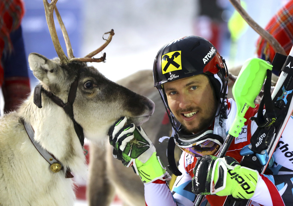 First placed Austria's Marcel Hirscher poses for a photo with a reindeer at the end of an alpine skiing men's World Cup slalom, in Levi...
