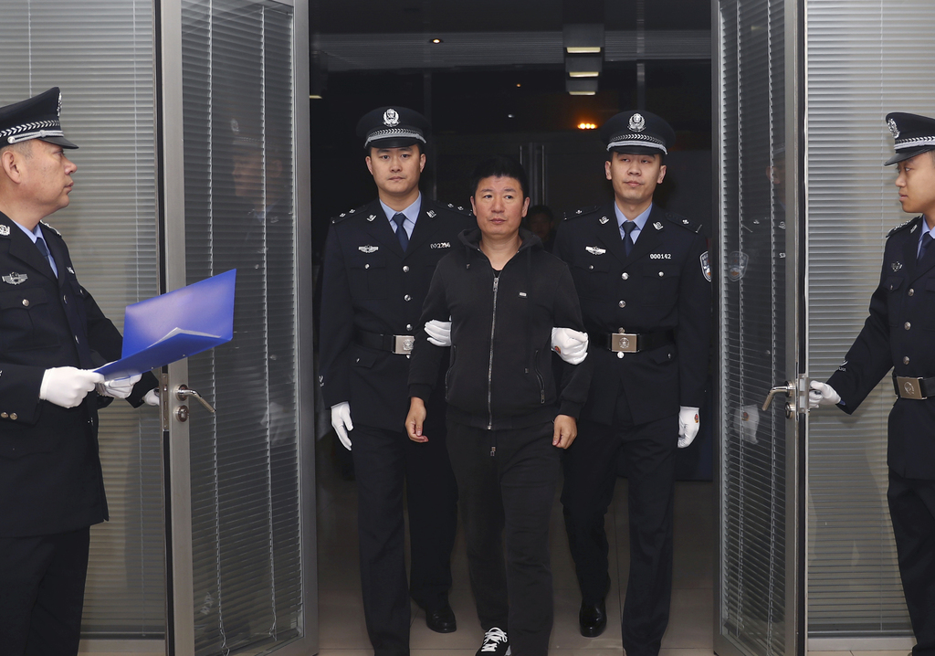 In this photo released by China's Xinhua News Agency, Yan Yongmin, center, arrives at Capital International Airport in Beijing, Saturda...