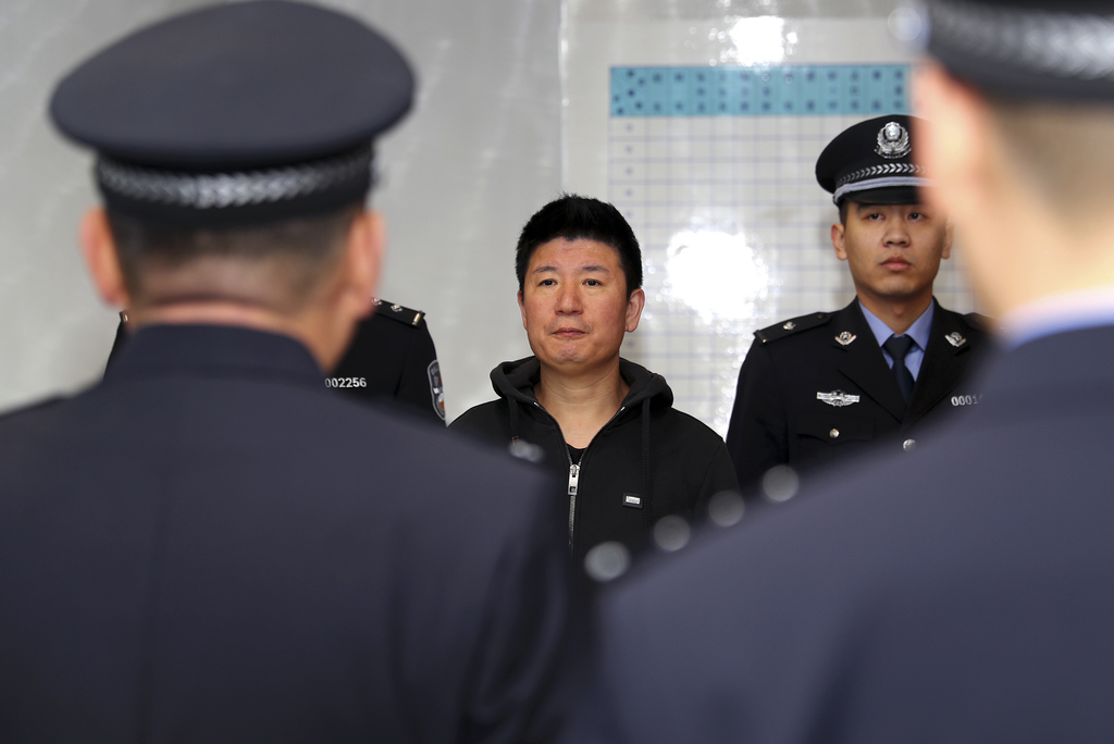In this photo released by Xinhua News Agency, Yan Yongmin, a graft fugitive who had been on the run for 15 years, arrives at Capital In...