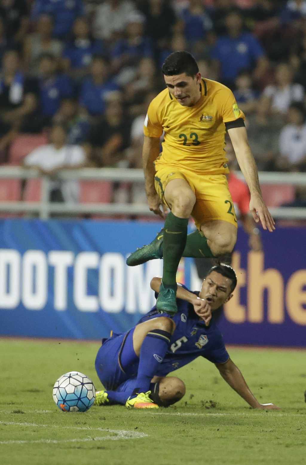Jackson Irvine of Australia jumps over Adison Promrak of Thailand battle for the ball, during their World Cup qualifiers soccer match a...