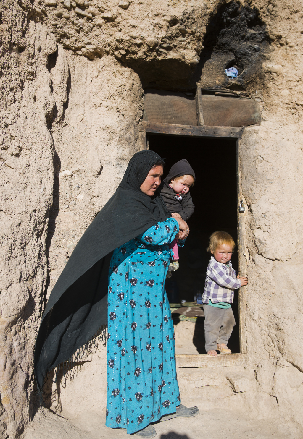 In this Monday, Nov. 7, 2016 photo, an Afghan mother, Marzia, 30, stands at the entrance of her cave after an interview with the Associ...