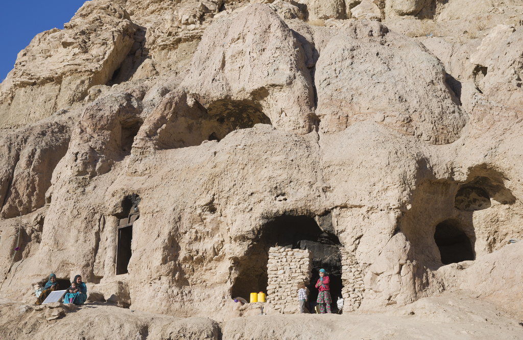 In this Monday, Nov. 7, 2016 photo, Shepha Qah, 8, and her brother stands at the entry of their cave in Bamiyan, Afghanistan. The cave-...