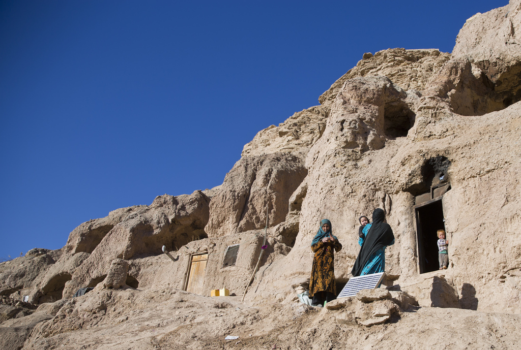 In this Monday, Nov. 7, 2016 photo, Marzia, 30, in blue, talks to her neighbor near her cave in Bamiyan, Afghanistan. Marzia and her hu...