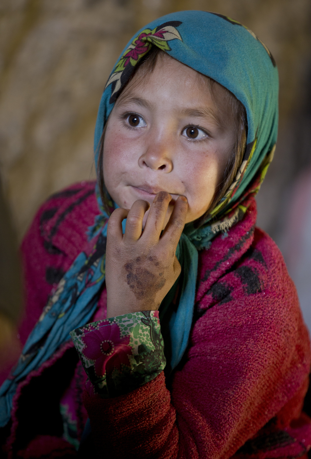 In this Monday, Nov. 7, 2016 photo, an Afghan girl, Shepha Qah, 8, listens during an interview with the Associated Press in their cave ...