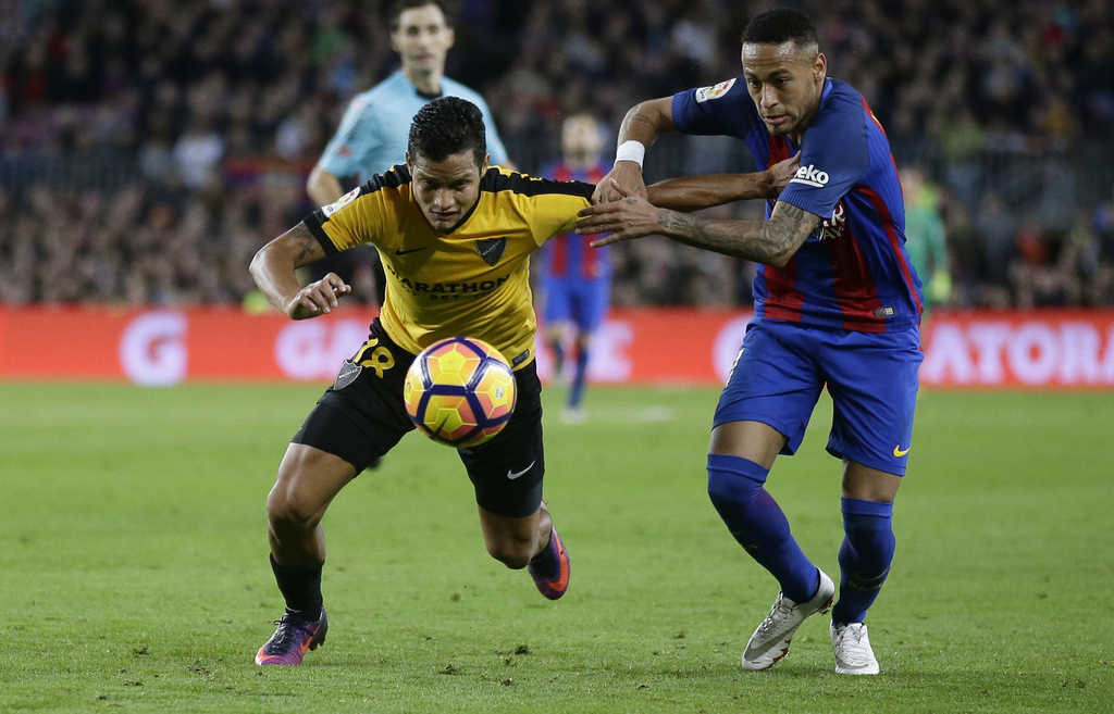 FC Barcelona's Neymar, right, duels for the ball against Malaga's Roberto Rosales during the Spanish La Liga soccer match between FC Ba...