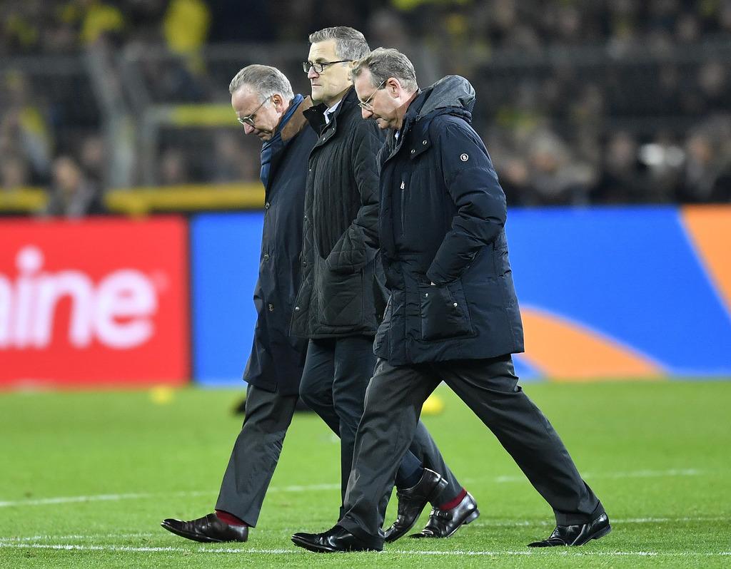 Bayern CEO Karl-Heinz Rummenigge, left, leaves the stadium after losing the German Bundesliga soccer match between Borussia Dortmund an...