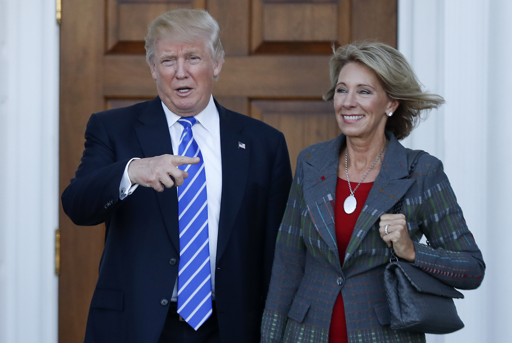 FILE - In this Nov. 19, 2016 file photo, President-elect Donald Trump and Betsy DeVos pose for photographs at Trump National Golf Club ...