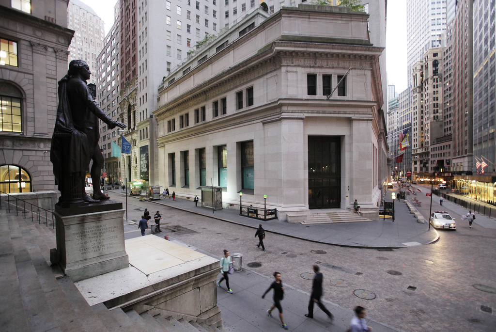 FILE - In this Oct. 8, 2014, file photo, people walk to work on Wall Street beneath a statue of George Washington, in New York. Health care and retail...