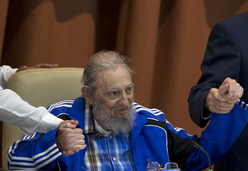FILE - In this April 19, 2016 file photo, Fidel Castro sits as he clasps hands with his brother, Cuban President Raul Castro, right, an...