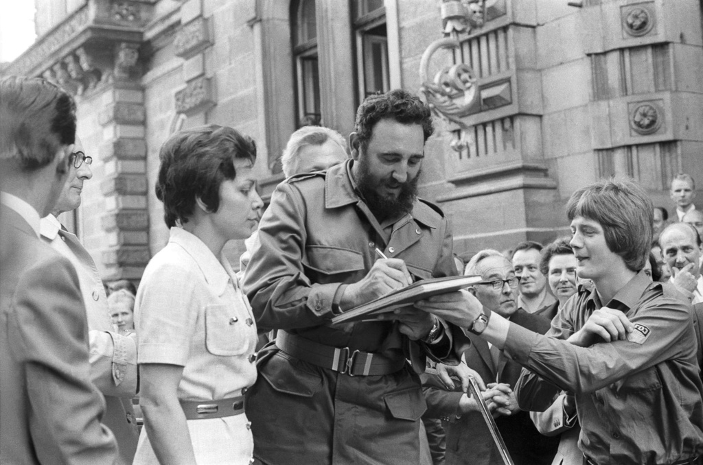 FILE - In this June 1972 file photo, Cuba's leader Fidel Castro autographs a book during his visit to East Berlin in the former German ...