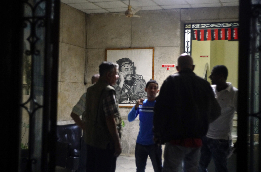 People gather at an office of the Popular Assembly decorated with a picture of Cuban leader Fidel Castro in Havana, Cuba, early Saturda...