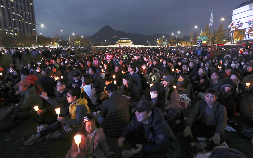 FILE- In this Saturday, Nov. 12, 2016, file photo, South Korean protesters hold up candles during a rally calling for South Korean Pres...