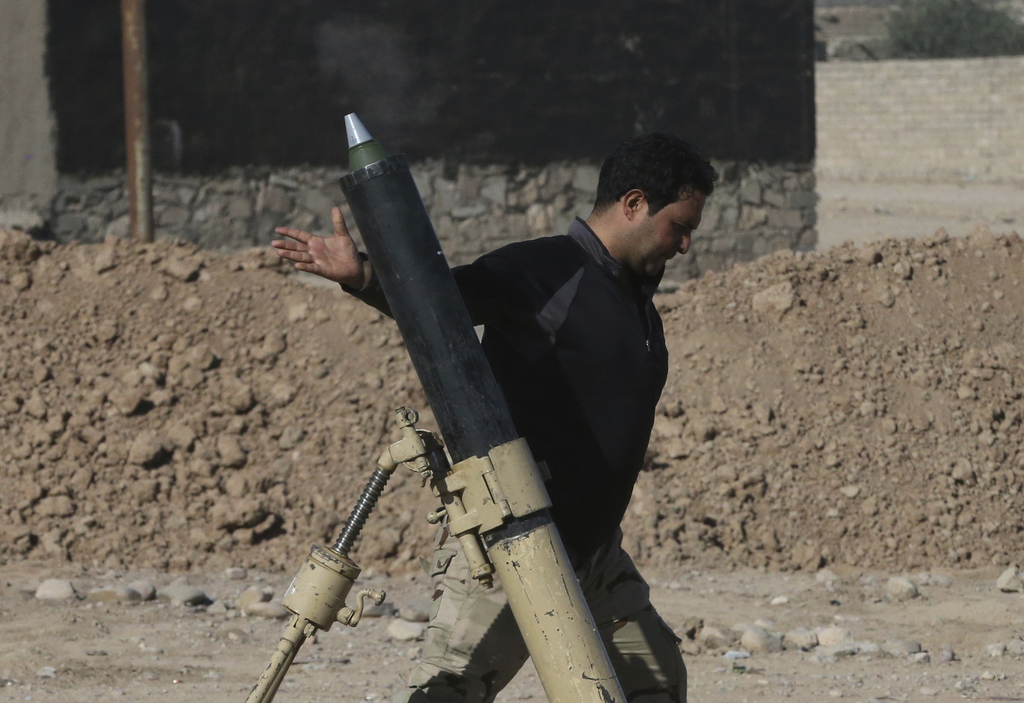 An Iraqi soldier fires a mortar shell against the Islamic State militants, in the Samah front line neighborhood, in Mosul, Iraq, Friday...