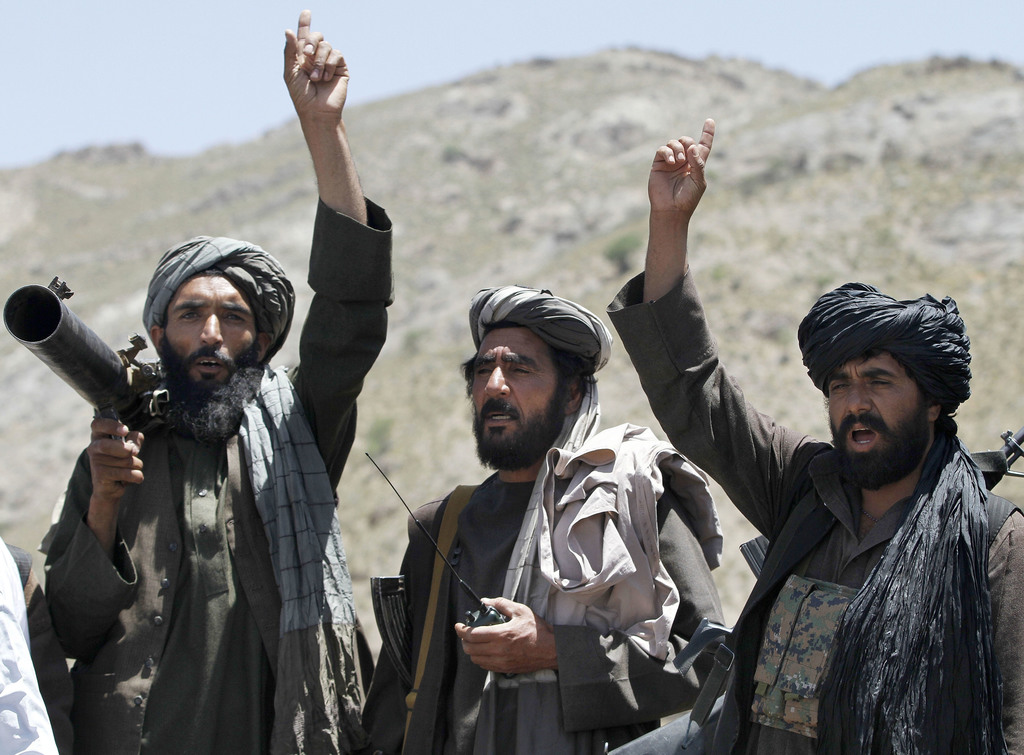 FILE - In this May 27, 2016 file photo, Taliban fighters react to a speech by their senior leader in the Shindand district of Herat pro...