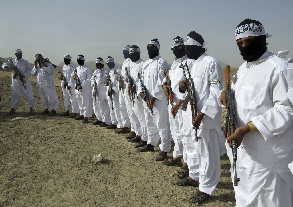 FILE - In this Aug. 15, 2016 file photo, Taliban suicide bombers stand guard during a gathering of a breakaway Taliban faction, in the ...