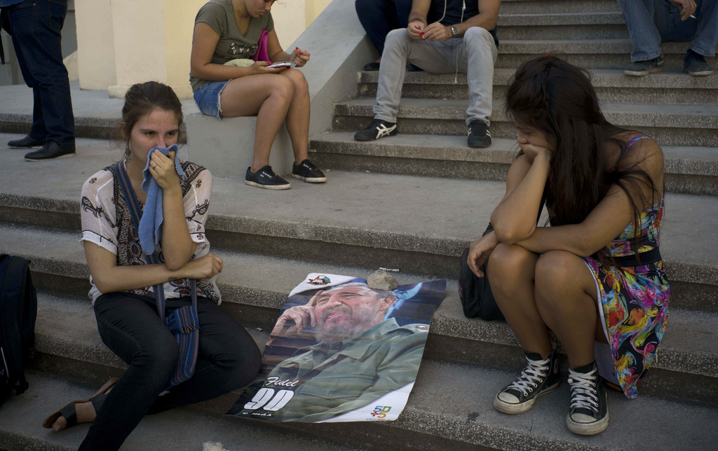 Young women join a gathering one day after the death of Fidel Castro in Havana, Cuba, Saturday, Nov. 26, 2016. Cuba will observe nine d...