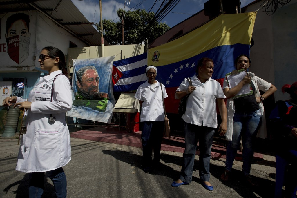 Cuban doctors working in Venezuela wait for pacients outside their clinic, where an image of Fidel Castro and a Cuban and Venezuelan fl...