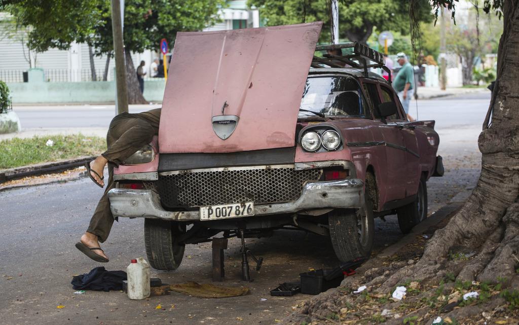 A man fixes his car in Havana, Cuba, Saturday, Nov. 26, 2016, the day after Fidel Castro's death. Cuba will observe nine days of mourni...